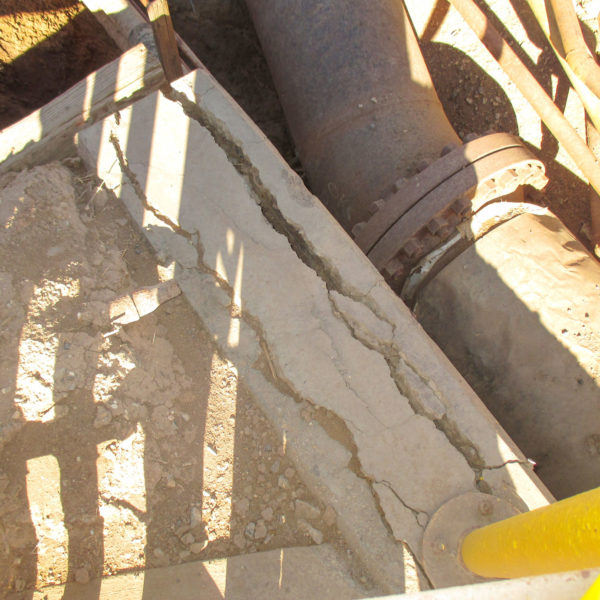 Looking down at a section of a damaged concrete trench wall and damaged pipe