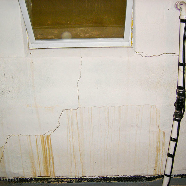 Closeup of bowing wall with cracks and leaks