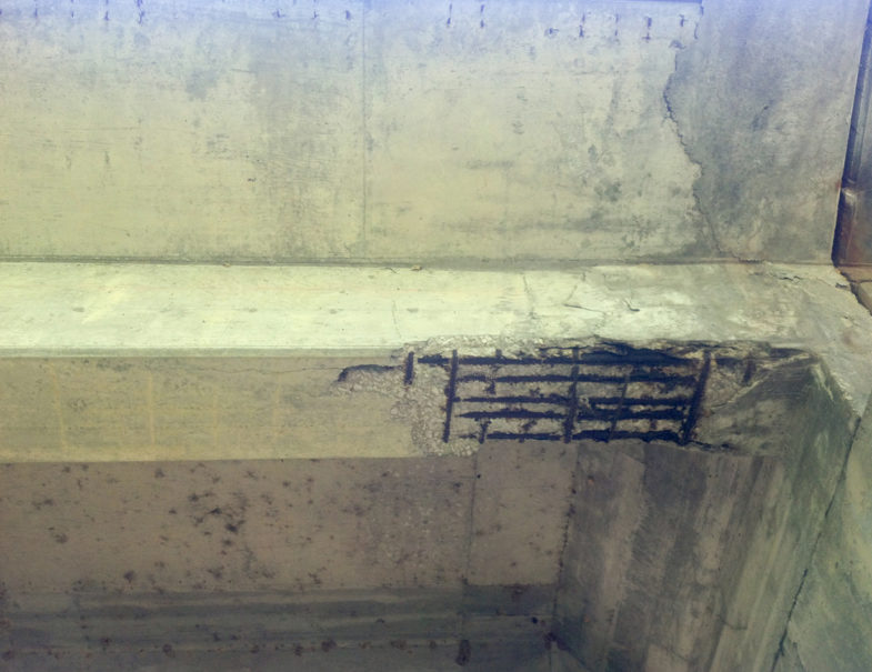 Support beam showing spalling and exposed, damaged rebar prior to repair.