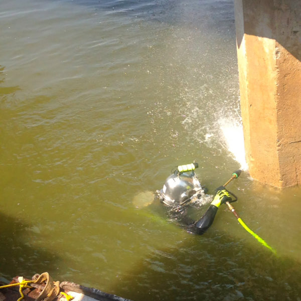 Diver cleaning a pile in preparation for CarbonSeal system application, above and below the waterline.