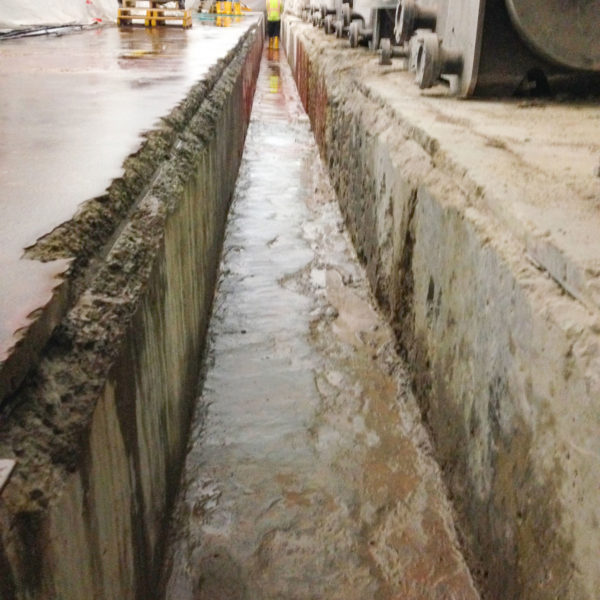 A badly damaged concrete trench showing acid damage and degraded concrete and coating.