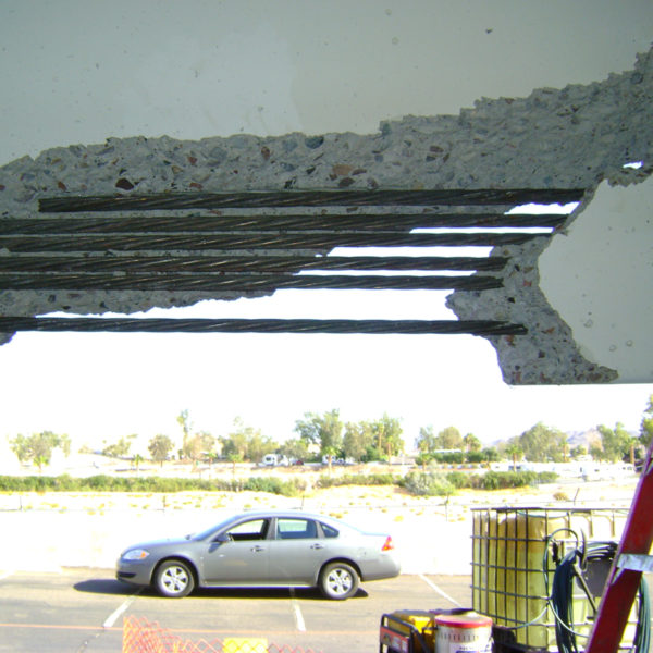 looking through a very large hole in a parking garage beam at the outdoor parking lot.