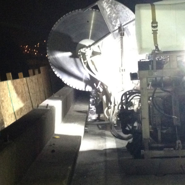 a giant walk-behind saw preparing to cut into the bridge for nighttime strengthening