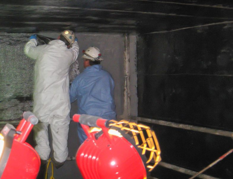 HJ3 team applying CarbonSeal carbon fabric to the prepared underground concrete tank wall.